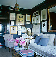 The wooden panelling of a snug informal living room is painted in black lacquer and every available inch of space on the panelled walls is taken up with the display of a wide-ranging collection of framed paintings and prints including Study For Self-Portrait by Michael Rainey