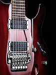 Artistic closeup of red electric guitar Ibanez with chrome parts on black background