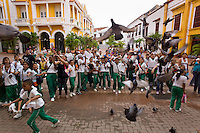School children chase pigeons on the Plaza San Pedro Claver in Cartagena, Colombia.