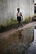 A young boy walks past a narrow alley at the transit camp in Badagabapur, in Jagatsinghpur, Orissa. Posco Transit Camp is being set up for people who have been driven out of their villages for being pro-Posco, where they live on the side of a highway on $80 a day shared between 195 people.