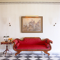 An antique sofa in the entrance hall, upholstered in crimson damask, above which hangs a painting of the early railway