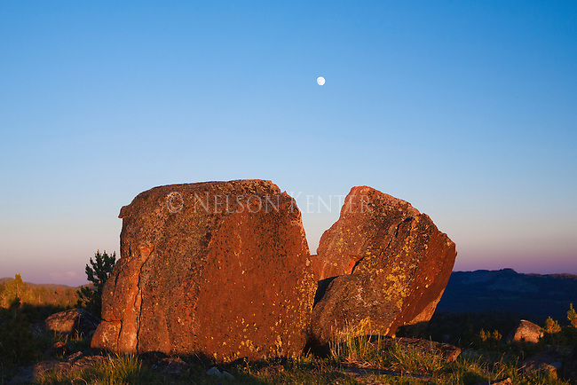 The moon rises as the sun lights rocks along the high lakes trail in the beartooth wilderness area