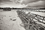 An old wooden fence and abandoned home sit in a snow-covered prairie in Central Montana.
