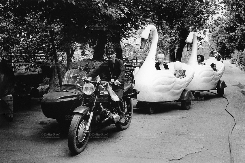 Kazakhstan. Semipalatinsk. Amusement park. A man riding a sidecar motorbike pulls two fake plastic swans carrying mothers and children.  Semey is the kazak name for Semipalatinsk and is located in the Eastern Kazakhstan Province. © 2008 Didier Ruef .