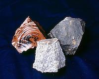 IGNEOUS ROCKS - Obsidian; Basalt; Granite<br /> Left: Obsidian -red, glassy; Center: Granite -dark gray, coarse grained, plutonic; Right: Basalt- extrusive, volcanic.