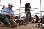 CHAD PILSTER &bull;&nbsp;Hays Daily News<br /> <br /> Cody Anthony, left, Monahans, Texas, works on preparing his saddle while James Greeson, Huntsville, Texas, tightens his chaps on Monday, July 29, 2013, during the Graham County fair and Jayhawker Roundup Rodeo in Hill City, Kansas.