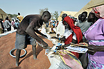 Displaced families receive sorghum during a food distribution by the United Nations World Food Program in Agok, a town in the contested Abyei region where tens of thousands of people fled in 2011 after an attack by soldiers and militias from the northern Republic of Sudan on most parts of Abyei. Although the 2005 Comprehensive Peace Agreement called for residents of Abyei--which sits on the border between Sudan and South Sudan--to hold a referendum on whether they wanted to align with the north or the newly independent South Sudan, the government in Khartoum and northern-backed Misseriya nomads, excluded from voting as they only live part of the year in Abyei, blocked the vote and attacked the majority Dinka Ngok population. The African Union has proposed a new peace plan, including a referendum to be held in October 2013, but it has been rejected by the Misseriya and Khartoum. The Catholic parish of Abyei, with support from Caritas South Sudan and other international church partners, has maintained its pastoral presence among the displaced and assisted them with food, shelter, and other relief supplies.