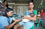 Lizel Abincula, a nurse-midwife at the public clinic in Bacubac, a neighborhood in Basey in the Philippines province of Samar, administers a polio vaccination to three-month old Eula Mae Caramol, as her mother, Carmelete Joy Caramol, holds the girl. The community was hit hard by Typhoon Haiyan in November 2013. The storm was known locally as Yolanda. The ACT Alliance has been providing a variety of forms of assistance to survivors here.