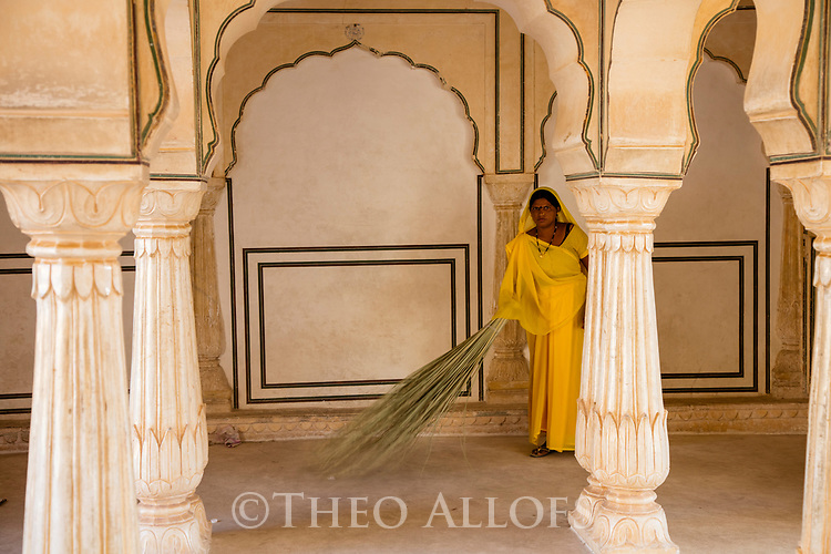 India,  Jaipur, Rajasthani woman cleaning a pillar hall at Jaipur Fort