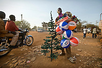 Street vendor in Juba selling plastic Christmas trees and inflatable balls, all made in China. Central Equatoria, South Sudan.