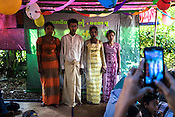 The bride and groom, Awe Mu (22) and Min Ko (21) pose for photos with their friends in Kant Ma Lar Chang Village in Pyapon district of Myanmar.
