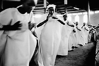 Burundi. Karuzi Province. Gitaramuka. Feast of the Assumption of the Blessed  Virgin. Religious service. Young women dressed with white tunics dance and pray God.   © 2000 Didier Ruef