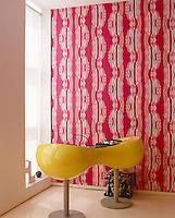 A yellow DJ mixing-desk pod with red patterned wallpaper behind it, both designed by Karim Rashid