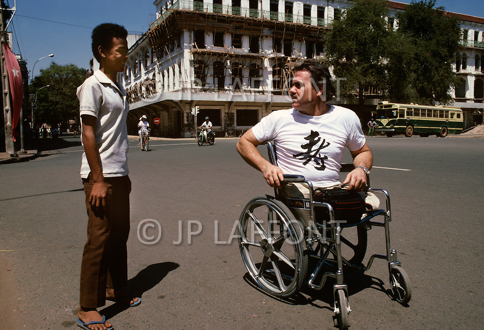 In Ho Chi Minh City, Saigon, February 1988. A veteran of Vietnam War, the american Bill Fero, wounded and amputed in 1971. Here, with an Amarasian on the Place of de l'Opera.
