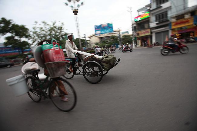 Bicycles, rickshaws and motorbikes go through a traffic circle one late afternoon in Nha Trang, Vietnam. July 13, 2011.