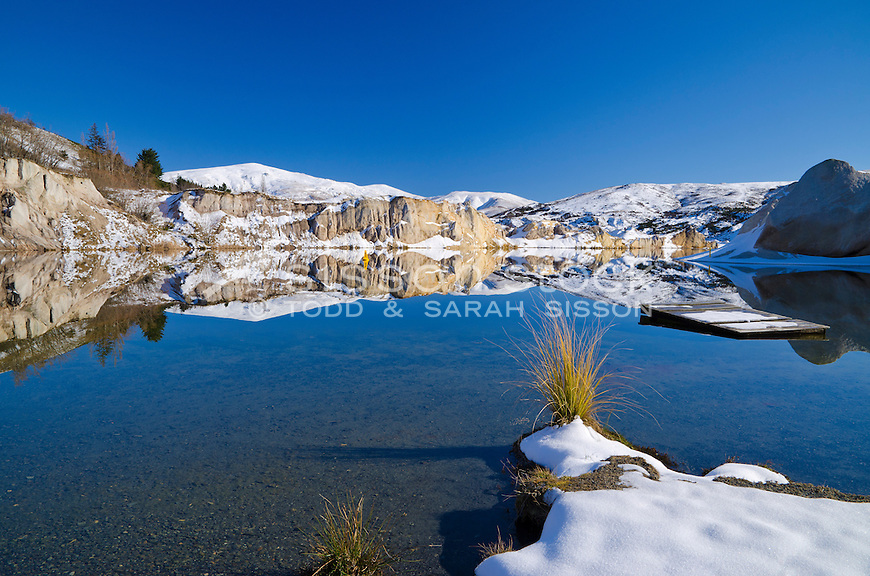 A perfect reflection of clay cliffs in the Blue Lake, St Bathans on a sunny blue sky day with pontoon on the lake. New Zealand