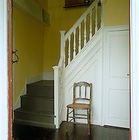 In the entrance hall the walls are painted a cheerful butter yellow with fresh white woodwork