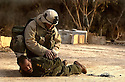 A U.S. Army 3rd Division 3-7 Task Force soldier takes a surrendering Iraqi Lieutenant Colonel into custody April 2, 2003 at an army outpost in the outskirts of Baghdad.