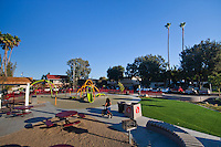 An overview of Circle Park, a pocket park located on Park Circle Drive in Anaheim, California.  This is a relatively wide-angle view of the park that places the park in the context of its surrounding parking and apartments.  Visible are play structures, an artificial-turf lawn, benches, a picnic / BBQ area, a red fence, and more.  A girl on a bike is prominently featured.