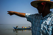 49 year old Win Shwe, the Chairman of the village fisheries society instructs the fisherman while on a boat on river Bogale near Damin Naung village in Pyapon district of Myanmar.