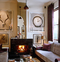 A pair of sofas flank a cosy fire in this living room and the walls are decorated with lithograph prints by Stephen Inggs