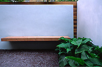 A simple wooden bench mounted into a floating wall flanked by Arum Lilies with chipped slate as ground cover