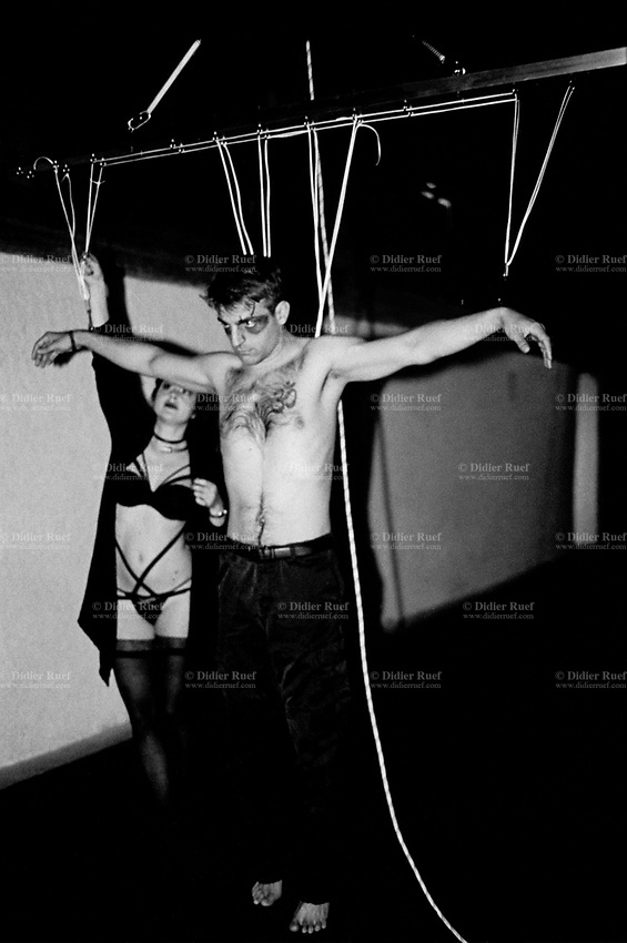 Switzerland. Canton Valais. Riddes A woman with sexy underwear is helping a man during a crucifix suspension. A suspension is the act of suspending a human body from hooks that have been put through body piercings. A crucifix suspension is a variation on a suicide suspension. A suicide suspension is a suspension in which the hook(s) are placed in the upper back, such that the suspendee is hanging upright. In the crucifix, hooks are also placed in the arms, such that the suspendee appears to be hanging on a cross, with his or her arms held out to the side. The suspendee's body is studied to decide the proper placement, number, and size of metal hooks which are pierced into the skin to lift the person off the ground. Depending on the position in which the body is to be suspended, multiple hooks are used. Finding the proper hook placement and number involves basic geometry and an acute understanding of human anatomy and physiology, as well as the durability of the individual's skin. If the number of hooks are too few, the suspended individual's skin will be unable to withstand the body's weight and will rip. The amount of weight that each hook supports must be distributed evenly throughout the entire body. A set of ropes are attached to the hooks in order to slowly and carefully lift an individual off the ground. 31.10.2016  © 2016 Didier Ruef