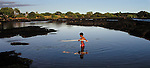 Samuel Brandon fishes with a sharpened stick in the low-tide pools about Na Alehu on the south side of the Big Island of Hawaii.