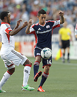 New England Revolution midfielder Diego Fagundez (14) attempts to control the ball as D.C. United defender James Riley (2) pressures. In a Major League Soccer (MLS) match, the New England Revolution (blue) tied D.C. United (white), 0-0, at Gillette Stadium on June 8, 2013.