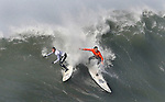 South African Chris Bertish (orange) edges out Grant Twiggy Baker to win the $50,000 first prize on day when several contestants lost control on monster faces and a rogue wave swept over spectators, injuring 13 and causing complete chaos.