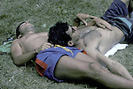 Gay couple alseep on grass being intimate during gay pride week