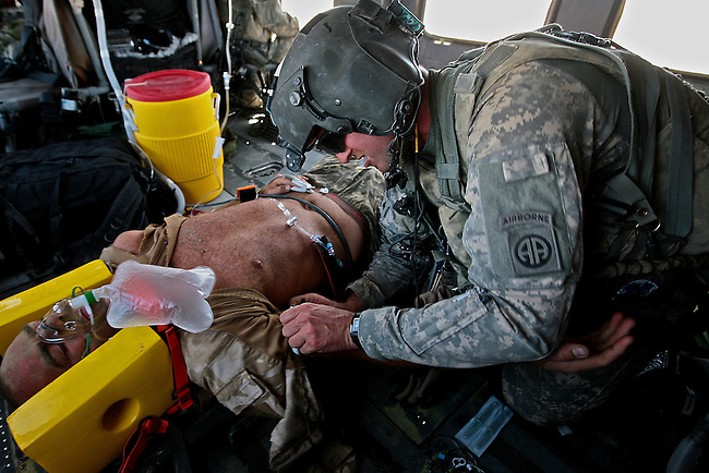 Flight medic Sgt. Nathaniel Dabney, 32, of Prescott, Ariz., strips the shirt off a British soldier wounded by the blast of a concussion grenade in Helmand province, southern Afghanistan. Dabney is a medic with Company C, 3rd Battalion, 82nd Combat Aviation Brigade, which has pulled dozens of injured NATO and Afghan troops from the battlefield since a major offensive began in the region earlier this month. July 17, 2009 DREW BROWN/STARS AND STRIPES