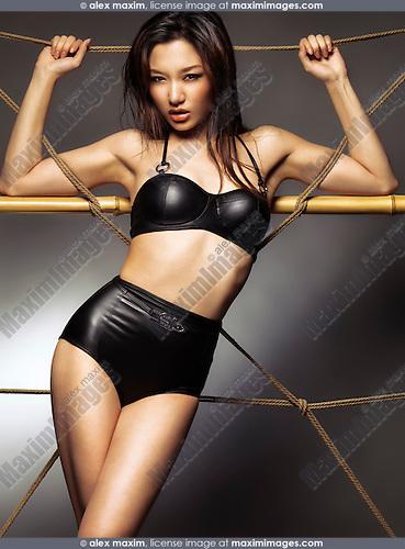 Edgy fashion photo of a beautiful sexy asian woman wearing a stylish black leather bikini swimsuit leaning against ropes