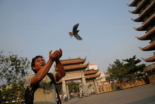 Bobby Calvan, of Sacramento, California, releases a bird, symbolizing hope, in front of a pagoda in Ho Chi Minh City, Vietnam.