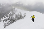 Snowboarder gets some air going off-run down Hurricane Ridge in the clouds.