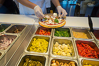 Employees construct a pizza right before the customers' eyes in assembly line fashion at the newly opened Blaze Pizza franchise in Newark, NJ on Saturday, 23, 2015. Blaze constructs its pizzas in a Chipotle style manner with the toppings put on catering to customers' individual preferences. (© Richard B. Levine)