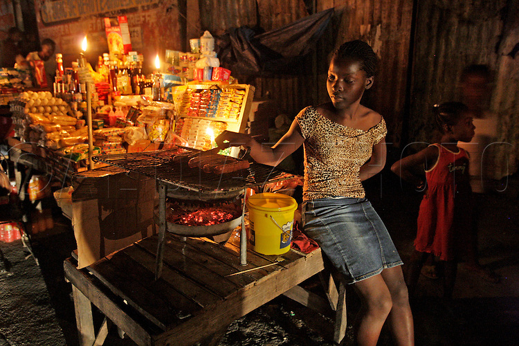 Street vendor Angie Gedeus, 18, tends to her grilling hotdogs on the side of the road in Port-au-Prince on March 3. 2010...