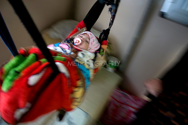 SULAIMANIA, IRAQ: A mother rocks her baby to sleep as women meet with Rezan.
