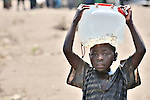A girl carries water in a camp in rebel-held territory in the eastern Congo. Families displaced by fighting between rebel Tutsi General Laurent Nkunda and the Congolese military took refuge in this camp they established in the shadow of a United Nations base in the village of Kiwanja. According to aid workers and human rights groups, rebel soldiers executed some 150 people here in a 24-hour period in early November. The killings took place half a mile from the UN base, yet the 120 UN peacekeepers, part of the largest UN peacekeeping contingent in the world, did not take any action to stop the violence. ...