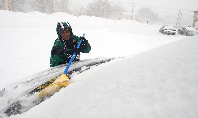 TORRINGTON, CT-021314JS05-Marie Mackey of Torrington, clears snow off her car after picking up pizza at the Pizza Hut in the Torrington Plaza as Thursday's snowstorm rolled through the area. <br /> Jim Shannon Republican-American