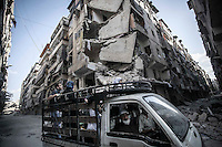 Syrian civilians drive by pass in front of a smashed buidings at the frontline in Bustan Al-Bashar/Al-Midan in Aleppo City.