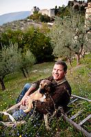Dr Rodney Lokaj, Medieval Philologist, with his dog 'Tilly' in the olive grove at 'I Cerri', Spoleto, Umbria, Italy