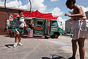 June 5, 2010. Durham, North Carolina..Locals play with hula hoops outside the Liberacion Juice Bus near the Durham Farmer's Market.. The Triangle has seen a recent boom in the number of mobile food trucks selling everything from tacos, to Korean BBQ, to fresh juices.