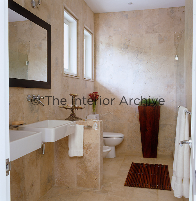 The walls and floor of the bathroom are tiled in sandblasted Saturnia marble