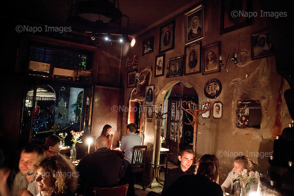 "KRAKOW, POLAND, SEPTEMBER 13, 2011:.Youths are chatting in the evening at the Mleczarnia bar in Kazimierz, former Jewish quarterof the town. Owner has decorated the walls with original vintage portraits that he collected all over Poland..(Photo by Piotr Malecki / Napo Images) ..KRAKOW, 9/2011:.Kawiarnia ""Mleczarnia"", dzielnica Kazimierz.Fot: Piotr Malecki / Napo Images"
