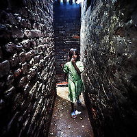 A young girl walks through the narrow alleyways of the Kathputli Colony. Located in northwest Delhi, Kathputli is inhabited by approximately 2,000 performing artists, practicing traditional art forms such as marionette puppetry, juggling, magic, acrobatics, dance and music. Many have travelled all over the world showcasing their abilities, but they still choose to remain living in this slum, which is one of the most impoverished in the city.