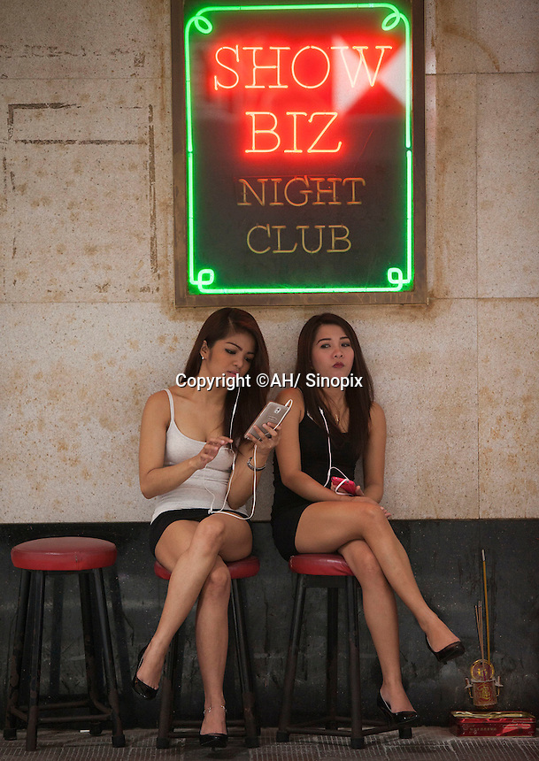 Girls sit outside a girlie bar in Hong Kong's Wanchai District.  A gruesome double murder was discovered yesterday of likely sex workers allegedly by a British banker who lived in the Wanchai District.<br /> <br /> 02-Nov- 2014
