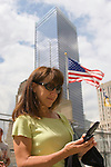 Woman on cell phone at ground zero in NYC with American flag and buildings in the background.