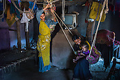 Rekha RAMESH (right) sits on a swing her son, Prahlad RAMESH while her older sister looks on in their house in Dhawati VIllage of Khaknar block of Burhanpur district in Madhya Pradesh, India.  Photo: Sanjit Das/Panos for ACF