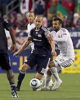 New England Revolution forward Rajko Lekic (10) dribbles as Vancouver Whitecaps FC defender Mouloud Akloul (50) defends. In a Major League Soccer (MLS) match, the New England Revolution defeated the Vancouver Whitecaps FC, 1-0, at Gillette Stadium on May14, 2011.